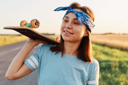 Outdoor shot of smiling brunette woman wearing casual style t shirt and hair band, holding skateboard on shoulders, looking away with smile, expressing happiness.