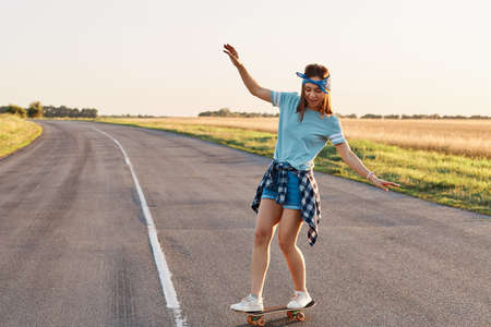 Sporty woman riding on the skateboard on the road., Slim sporty female enjoying longboarding, raising hands, having happy concentrated expression, healthy lifestyle, copy space. 免版税图像