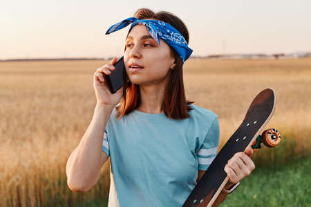 Attractive dark haired woman talking on smartphone with skateboard outdoor in field, waiting friends for skateboarding together, wearing t shirt and hair band. 免版税图像