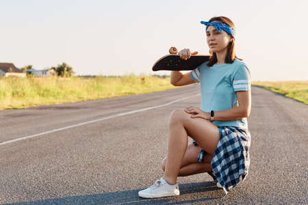 Young adult attractive girl with dark hair posing with a longboard over shoulders while sitting on the road in summer, looking away with pensive expression.