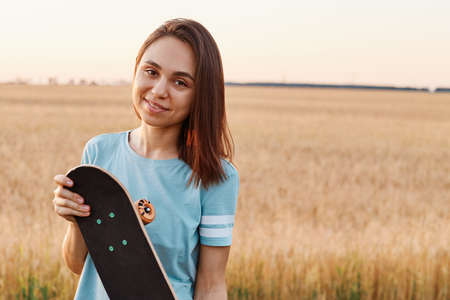 Portrait of charming brunette woman wearing blue t shirt looking directly at camera, holding skateboard in hands, copy space for advertisement, healthy lifestyle. 免版税图像