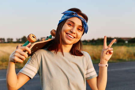 Outdoor photo of pretty brunette female wearing t shirt and hair band looking at camera with toothy smile and showing thumb up, expressing positive emotions. 免版税图像