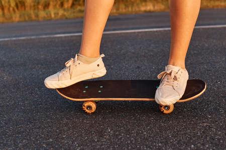 Faceless female in white shoes riding longboard on asphalt road, unknown person skateboarding alone, girls legs on skateboard. 免版税图像