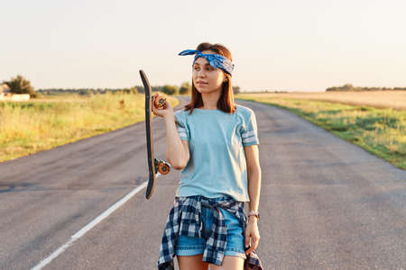 Outdoor shot of beautiful dark haired woman wearing hair band, t shirt and short, holding longboard in hands and looking away with thoughtful expression. 免版税图像