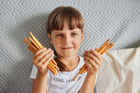 Portrait of charming dark haired girl holding pretzels sticks in hands and looking directly at camera, female child wearing white t shirt, has pigtails, posing at home while sitting on sofa. 免版税图像