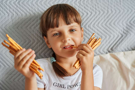 Portrait of preschooler female kid with dark hair and pigtails wearing white casual style t shirt holding in hands and biting pretzels sticks, looking at camera with satisfied facial expression. 免版税图像
