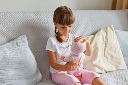 Photo of preschooler girl sitting on the sofa in the room at home playing with baby doll like mom, child wearing white t shirt and pink short, childhood.