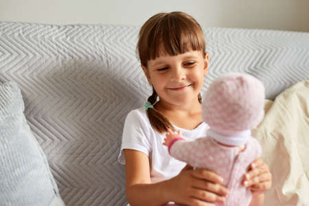 Smiling happy charming kid with dark hair and pigtails holding in her hand a doll, looking at toy with smile, kid wearing white casual t shirt playing indoor. 免版税图像
