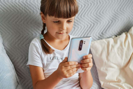 Caucasian little girl sitting on the sofa with mobile phone in hands, dark haired female kid playing games on smart phone, wearing white casual style t shirt. 免版税图像