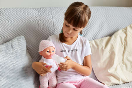 Indoor shot of little girl sitting on the sofa in the room at home playing with baby doll, like mom, dark haired preschooler female child holding toy. 免版税图像