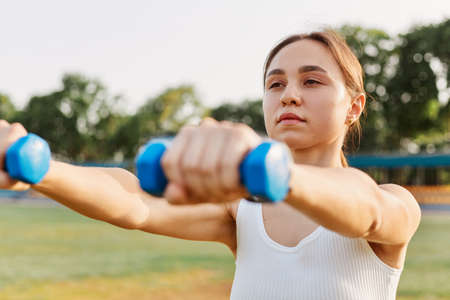 Fitness girl workout with dumbbells, sporty woman in sportswear doing intense exercise outdoor in stadium, training for strong muscular body, wearing white top. 免版税图像