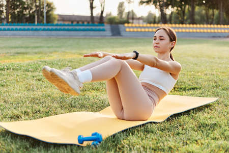 Full length portrait of sporty attractive slim woman with dark hair and ponytail doing fitness for abs, raised arms and legs, workout outdoor in stadium.