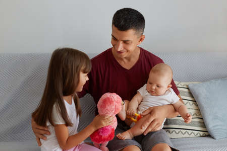 Young happy beautiful family relaxing at home. Father and two children sitting on sofa, elder daughter showing her new toy to little charming kid, dad with kids playing together.