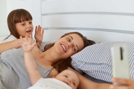Happy positive female lying in bed with her children and holding smart phone in hands, people waving hands ans say hello, family blog, online conversation with followers.