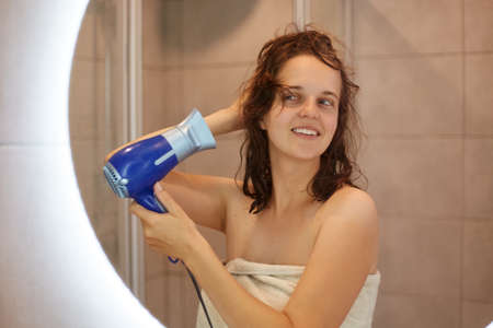 Image of pretty female looking in mirror while drying her hair with hair dryer, standing with naked shoulders, being wrapped in white towel, morning procedures.