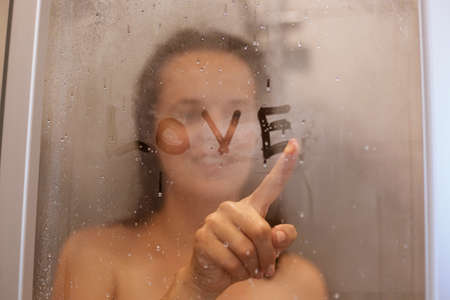 Portrait of cheerful woman drawing ward love on condensed glass door, looking with smile, expressing romantic feelings, morning procedures, skin and hair care.