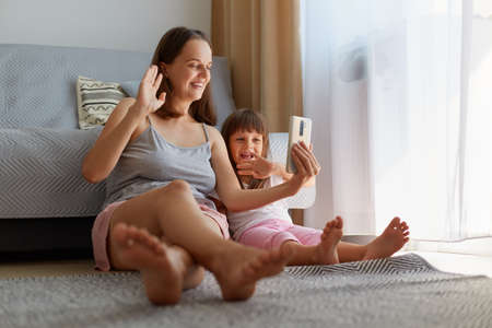 Indoor portrait of happy positive female with her charming daughter holding smart phone and waving hands while having livestrem or video call, family sitting near sofa on floor at home. Archivio Fotografico