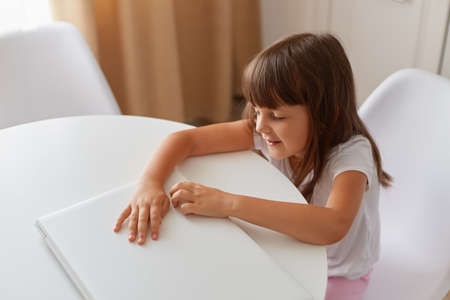 Cute little girl is sitting at table with her white closed laptop, dark haired female child posing in light room wearing casual style closing, indoor shot. Archivio Fotografico