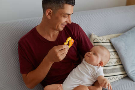 Happy father holding toy and playing with his baby boy or girl while sitting on sofa, smiling man wearing maroon t shirt showing to child orange fish, happy parenthood.