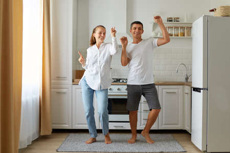 Indoor shot of happy positive husband and wife dancing, having fun together in the kitchen, celebrating relocation, being in good mood, expressing happiness.