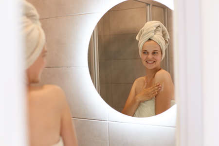 Skin care, cosmetology, daily procedures. Reflection in the mirror of woman use skin care products at home in light bathroom, having happy expression, being wrapped in towel.