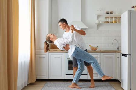 Happy couple dancing in the kitchen, husband and wife wearing white shirts dance in morning near the window, expressing love and romantic feelings, indoor shot.
