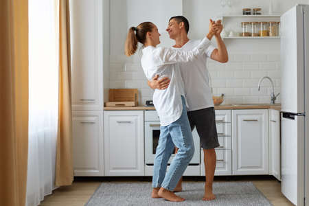 Full length portrait of happy smiling husband and wife dancing together in at home in light room, with kitchen set, fridge and window on background, happy couple.