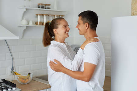 Indoor shot of smiling female hugging with her husband at home in light kitchen, happy couple standing together and looking at each other with love and romantic feelings. Archivio Fotografico