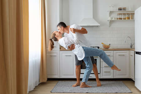 Full length portrait of happy couple wearing casual clothing dancing together in kitchen, husband kissing his wife, being happy to spend time together at home.