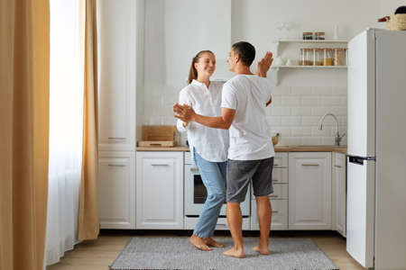 Full length portrait of happy positive falling in love couple dancing in kitchen together, spending time together at home, expressing romantic feelings.