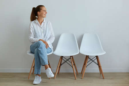 Indoor portrait of young attractive woman sitting on chair in waiting room, wearing jeans and white t shirt, looking away with charming smile, expressing positive emotions. Archivio Fotografico