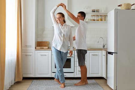 Indoor shot of happy couple having fun in kitchen, dancing together, handsome young husband holding beautiful wife hand, moving to favorite music, enjoying pastime together. Archivio Fotografico
