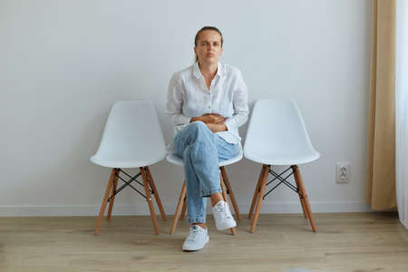 Portrait of sick woman with dark hair and ponytail, wearing white shirt and jeans, sitting on chair in queue to the doctor in clinic, suffering from terrible stomachache.