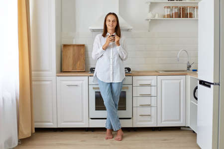 Full length portrait of a calm woman holding a cup of tea or coffee in her kitchen, attractive female wearing white shirt and jeans enjoying hot beverage at breakfast. Archivio Fotografico