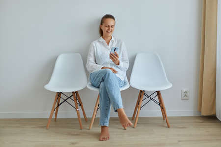 Indoor shot of attractive woman with dark hair and ponytail, wearing white jeans shirt and jeans, holding smart phone, surfing internet or checking social networks while sitting on chair.