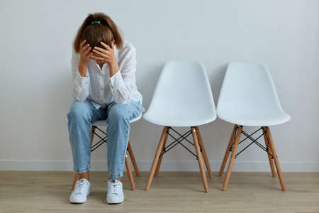 Indoor shot of depressed woman wearing casual attire sitting on chair with tilted head, having problems and troubles, expressing sadness, keeping hands on her face.