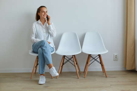 Attractive woman with ponytail wearing casual attire talking phone while sitting on chair against light wall indoor, looking away, expressing positive emotions.
