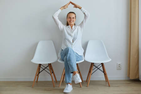 Good looking optimistic female sitting on chair indoor, wearing white shirt and jeans, making roof with hands above her head, feels safety, expressing happiness.