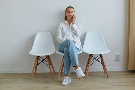 Indoor shot of astonished female wearing jeans and white shirt taking phone while sitting on chair, hearing shocked news, having surprised facial expression, keeps mouth open.
