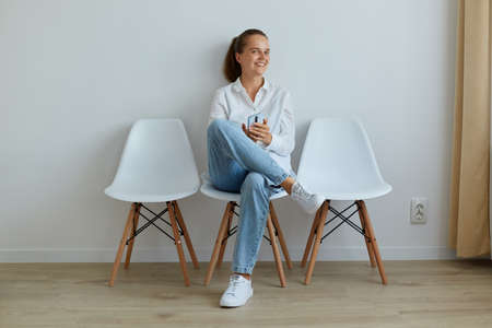 Smiling happy woman with toothy smile, holding smart phone in hands, looking at camera, sitting on chair, wearing jeans and white shirt, expressing positive emotions,