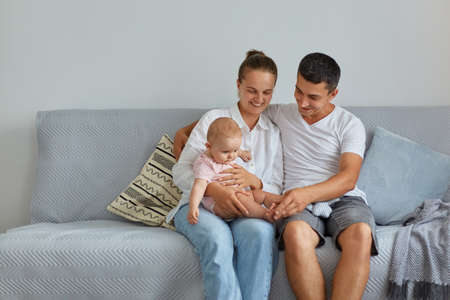 Portrait of happy family sitting on sofa in living room, people wearing casual clothing, spending time with their infant baby at home, parenthood, childhood. Archivio Fotografico