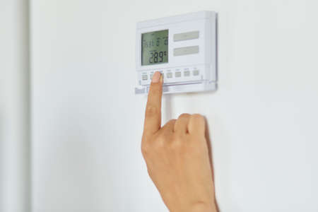Close up shot of woman hand regulating heating temperature with wireless thermostat on the white wall at home, unknown female pressing buttons, smart-home. Archivio Fotografico