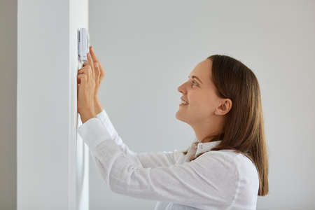Side view portrait of smiling dark haired female wearing white shirt regulating heating temperature with thermostat on the white wall in light room, smart home. Archivio Fotografico
