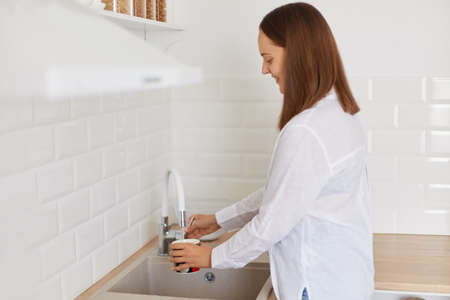 Side view portrait of dark haired woman wearing white shirt standing near kitchen set, pouring water from faucet in the kitchen, washing mug, posing indoor in light room.