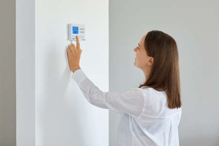 Indoor shot of young adult woman regulating heating temperature with a modern wireless thermostat installed on the white wall at home. Smart home heating regulation.