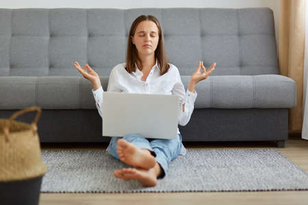 Portrait of relaxed female wearing white shirt and jeans sitting on the floor with laptop computer on legs, keeping hands in yoga gesture, trying to calm down and have rest.