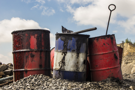 Empty metal barrels in the iron quarry in Ukraine Stock Photo