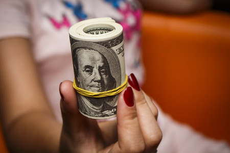 one hundred dollars: The girl holds a lot of bills of one hundred dollars Stock Photo