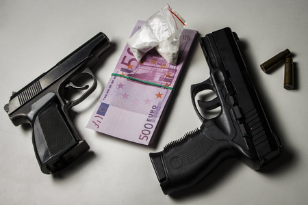 Black gun with a pack of euros and packets of drugs on a white table