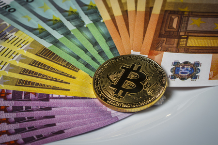 Bitcoin coin on a pile of euros on the table